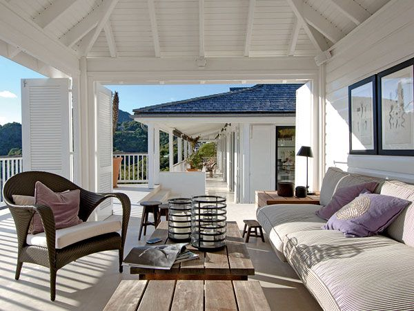 This casual built-in bench sits plenty of guests or becomes a great place for a nap. A striped outdoor fabric and wooden coffee tables ensure this space will withstand weathering. (Photo: Jean-Philippe Piter)
