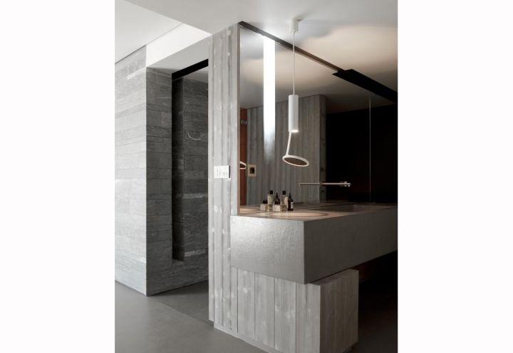 La stanza da bagno dello chalet firmato da Noé Duchaufour-Lawrance con arredi su misura in pietra locale e cemento. La lampada Loup-O Ceiling è di Kundalini, mentre la rubinetteria è di Boffi