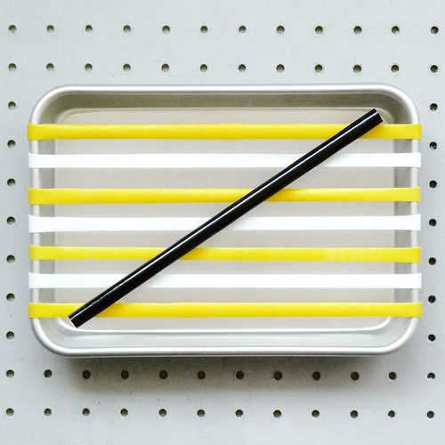 Pen tray, yellow & white elastic bands, pencil.