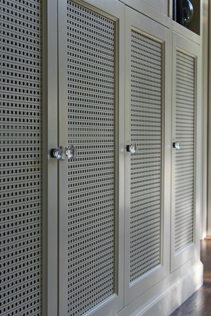 Put all that TV-related stuff inside cabinets, and put vented doors on the front so the electronics dont overheat. Beneath the TV, Stephanie designed doors with Octagon Cane Decorative Perforated Metal.