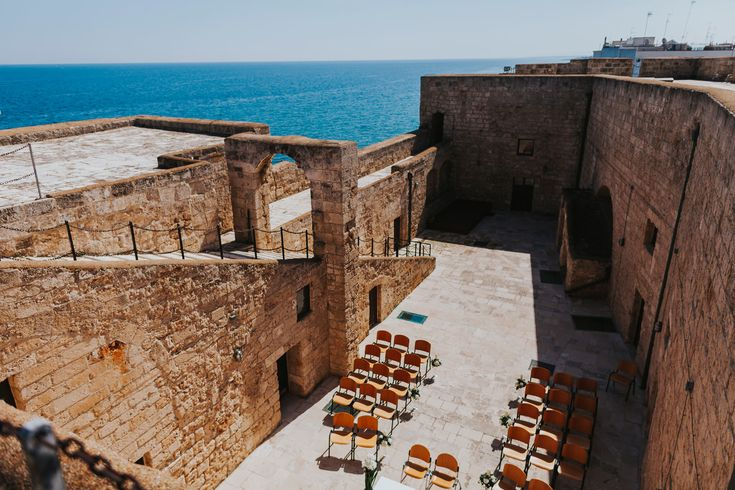 The beautiful coastal ceremony setting on top of the Castle of Carlo V in Monopoli, Italy. Photo by Benjamin Stuart Photography #weddingphotography #italianwedding #destinationwedding #weddingvenue #outdoorwedding #seaview #weddingday