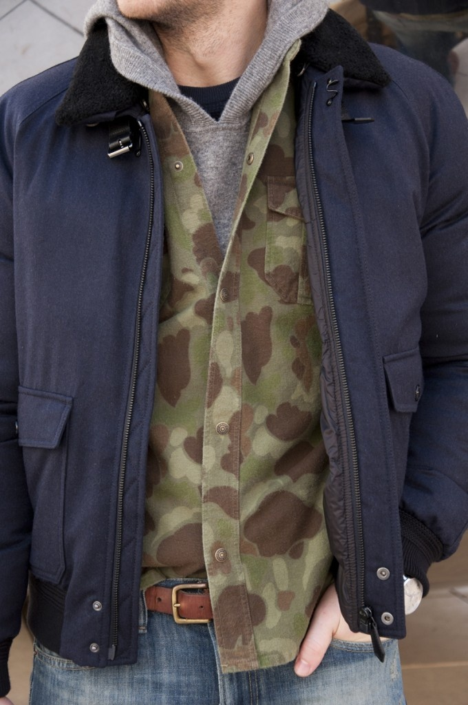 Jacket by Burberry, Camo overshirt by Gant, Hoody by T by Alexander Wang – All available at Nordstrom locations and Nordstrom.com. Jeans by Ralph Lauren Denim & Supply. Belt by Banana Republic. Boots by Red Wing. Shades by Persol. Watch by Montblanc.