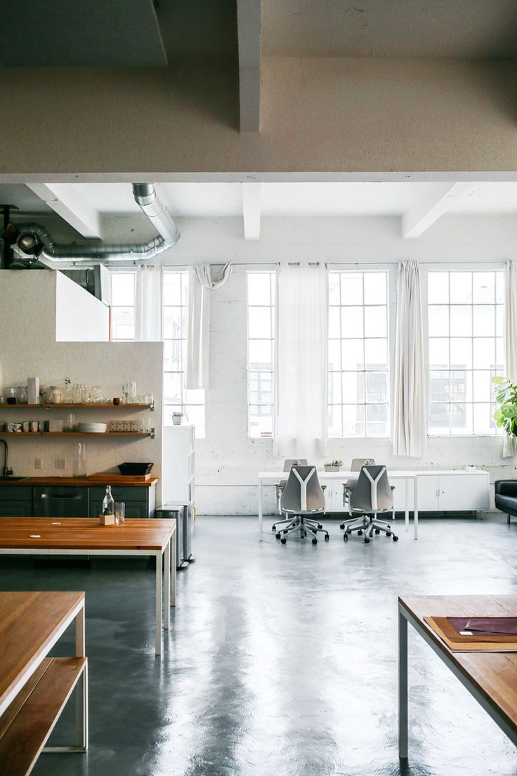 A lofty white space with small desks and chairs