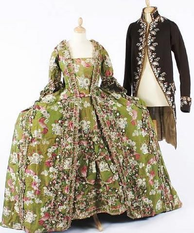 An 18th century wide French open court robe of silk damask with a woven floral and ribbon design worked in shades of green, pink and cream to a background of shot green and pink, with a sack back, underskirt, and a later made stomacher…