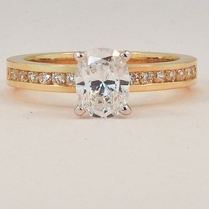 18K Yellow Gold Petite Channel Set Round Diamond Ring. Set with a 0.72 Carat, Ov…