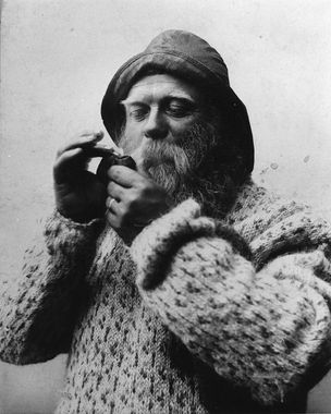 DigitaltMuseum - Portrett av mann med sydvest, skjegg og genser. Tenner på pipa.