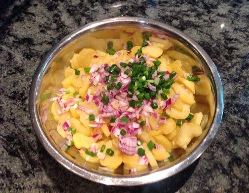 Für den klassischen Erdäpfelsalat nach Wiener Art zunächst die Erdäpfel mit der Schale kochen. Anschließend schälen und noch warm dünnblättrig in
