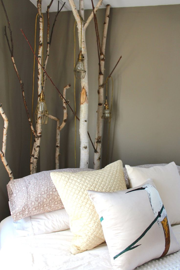 Birch branches behind a kitty-corner bed, with hanging lights... great use of space!