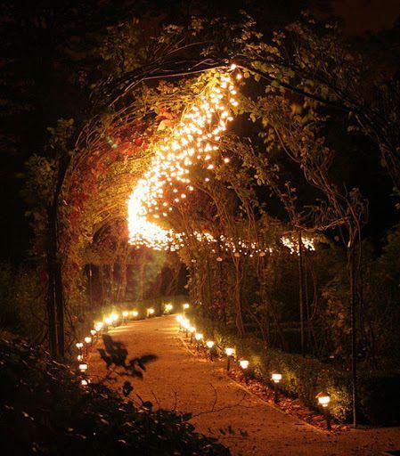Toegangsboog, overdag gekleurd lint, 's nachts vol met lichtjes...
