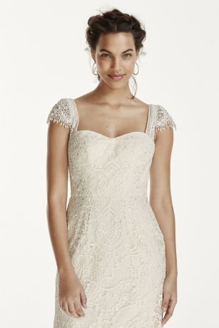 This vintage, romantic sheath is ultra feminine and the perfect choice for today's romantic bride!   Gown features allover battenburg lace with soutache sleeves.    Delicate pearls dangling at sleeves adds to the vintage look.   Open key-hole back adds extra back detail and drama.  Sweep train. Sizes 0-14. Ivory available in select stores and online.  Fully lined. Imported polyester. Button back closure. Dry clean only.  Also available in Petite,
