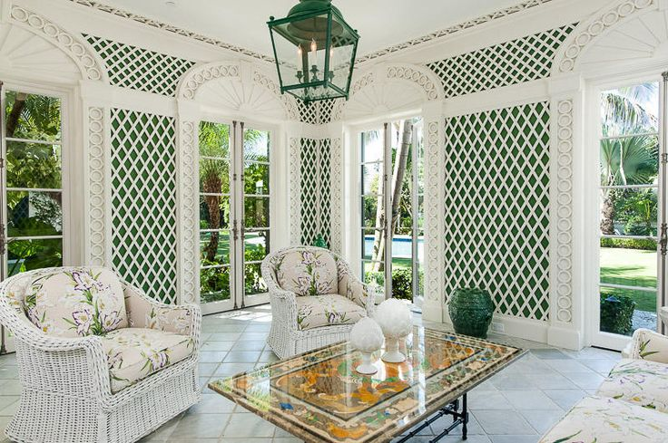 This Miami home has an open sunroom with white tile flooring, white wicker furniture with floral cushions, ornate french doors and green and white diamond pattered walls.