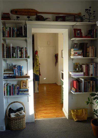 Creative Use of Space in a Studio Apartment bookshelves around doorway.