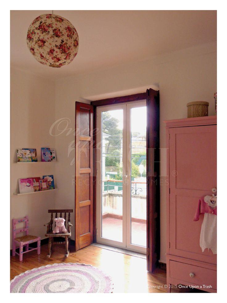 QUARTO DE BEBÉ CASCAIS * By Once Upon a Trash Prateleiras para livros colocadas junto à janela; Cadeiras de criança antigas (cadeira alentejana cor de rosa e cadeira de baloiço em madeira); Candeeiro de tecto em tecido estampado.
