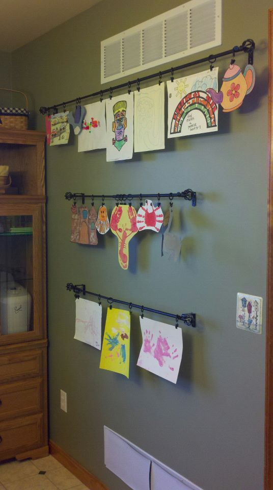 Hang drapery rods on your wall to display kids artwork. Drapery rods and drapery clips were purchased at Bed, Bath & Beyond.