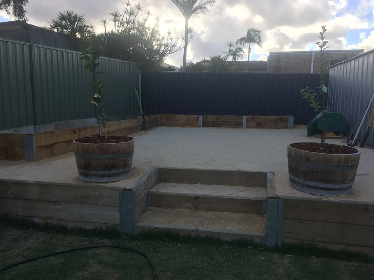 Backyard renovation DIY - top outdoor seating area, crushed limestone, wooden sleeper dividers and planter boxes, steps, wine barrels with lemon and lime trees