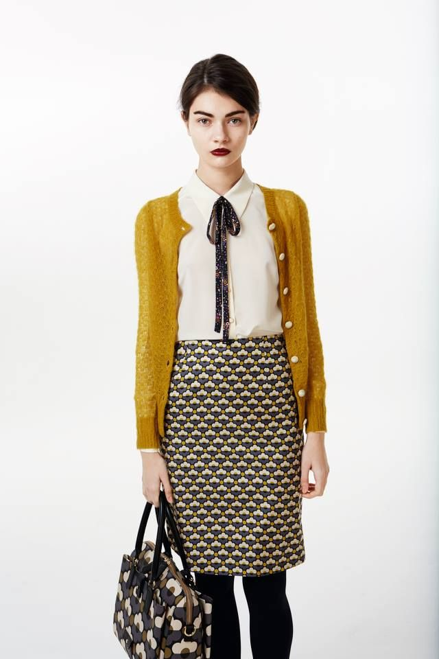 Ensemble by Orla Kiely--mustard cardigan over white blouse with a patterned bow tie. Cute patterned skirt and bag, too!
