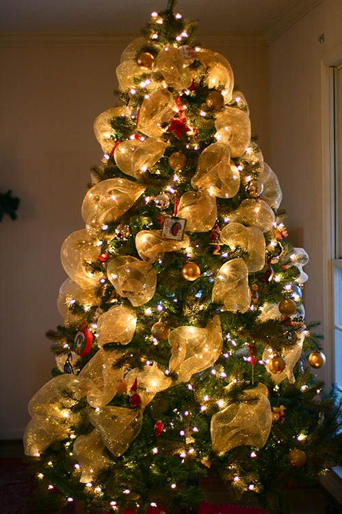 Deco mesh garland spiraled around tree instead of wrapped around it. I love the look!