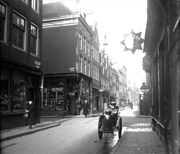 1930. A view of the crossing of Tweede Rozendwarsstraat and Rozenstraat in the Jordaan neighborhood of Amsterdam. In the background, passed the crossing, the Tweede Laurierdwarsstraat. At the corner of Rozenstraat and Tweede Laurierdwarsstraat lighting store Heman. In the '80's and '90's many of the buildings on the Rozenstraat and Tweede Rozendwarsstraat have been restored or demolished and rebuild. Stadsarchief Amsterdam / Nico Swaager. #amsterdam #1930 #TweedeRozendwarsstraat #Jordaan