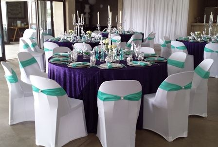 Purple tablecloths, white chaircovers, teal bands & teal napkins, candle holders on mirrors