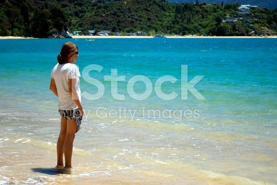 Paddling Woman looks in Sea, Kaiteriteri, New Zealand royalty-free stock photo