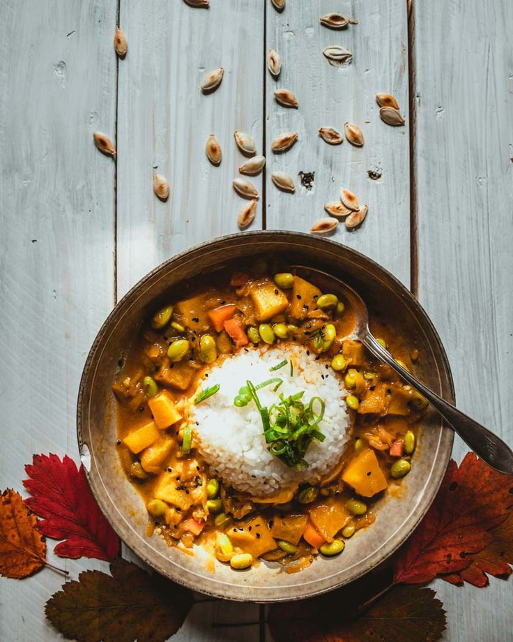 A fun shot of a bowl of curry with some autumn leaves acting as a table and pumpkin seeds falling from above. Perfect recipe for cold winter days. Vegan Curry. Variations of Katsu Curry #winterrecipes