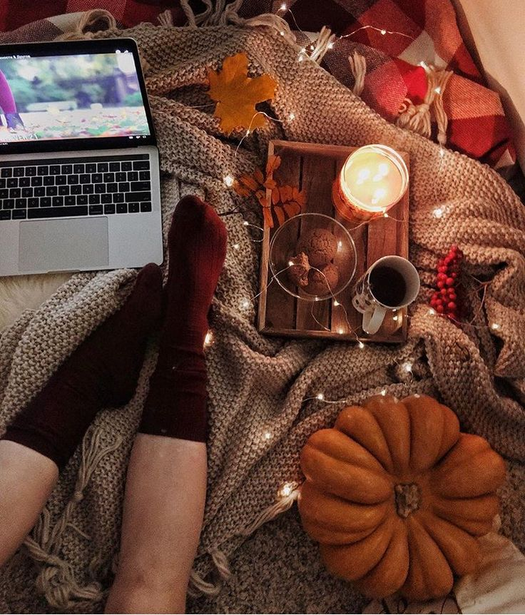 autumn and fall aesthetic | burgundy socks, pumpkin, cozy knit blankets, string lights, candle, leaves, movies