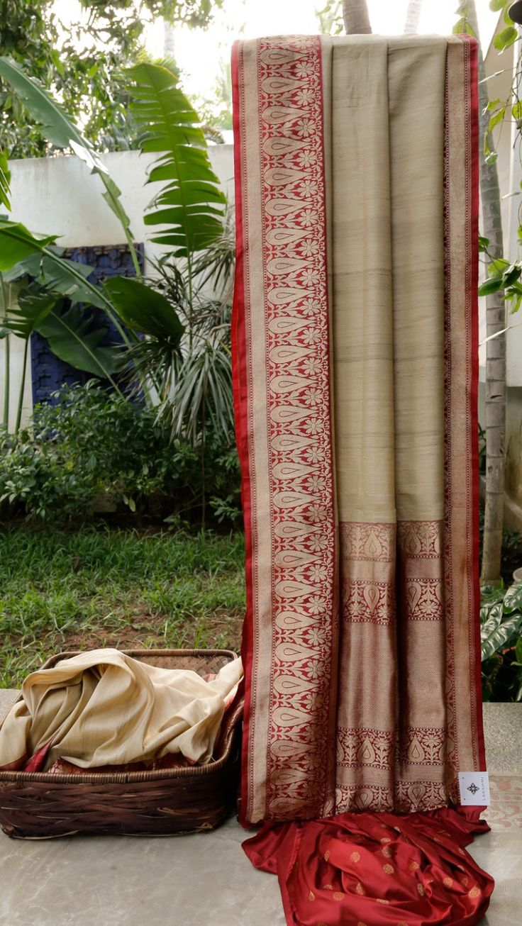 This simple sari is an oat tan coloured Benares tussar. The border is in garnet red with gold zari work while the pallu is in garnet red and blush red with gold zari work adding to the sophisticati…