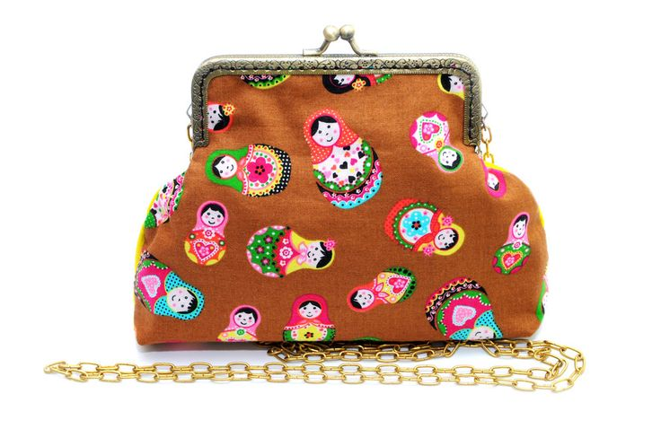 Lovely matryoshka pattern was mixed with bright yellow cotton fabric. The back side of the bag can be different, you choose the color/pattern you like. It is padded inside. It has been sewn to metal clutch frame and comes with chain. Size: 13 x 19 cm