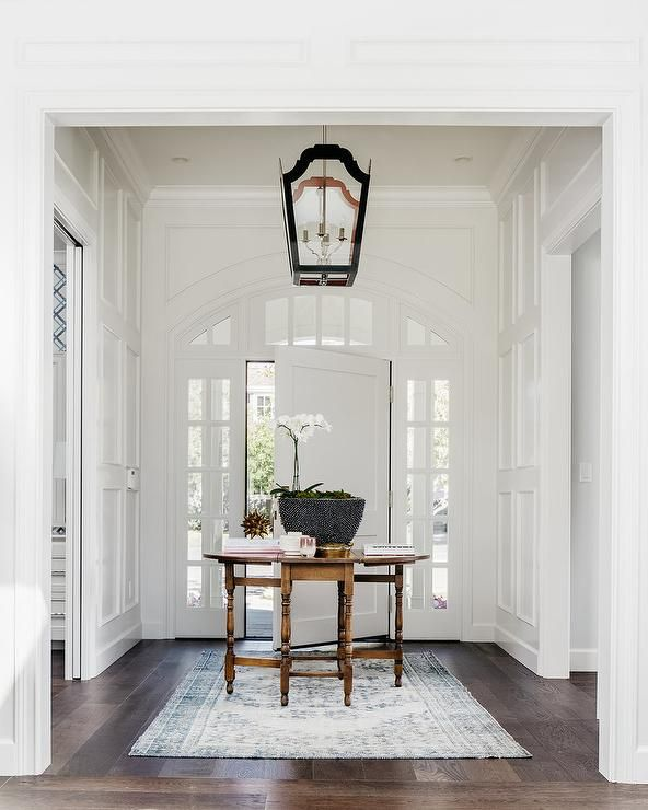 A white front door framed with arch windows and sidelights open to a foyer filled with a round wood table, placed in the center of the room, placed atop a white and blue rug illuminated by a black lantern.