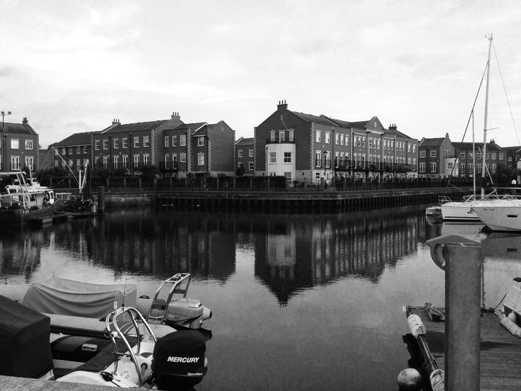 in this photo i made it black and white because it shows the reflection of the buildings in the calm water