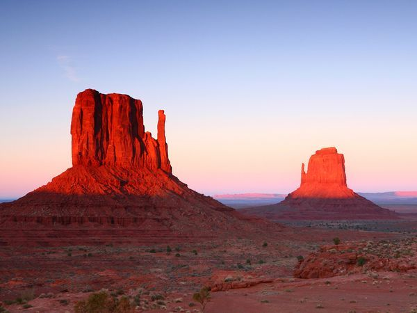 Sandstone buttes known as the Mittens tower over the desert floor in Monument Valley Navajo Tribal Park, Arizona.