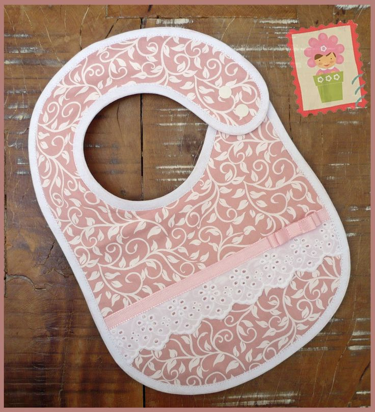 Babador rosa flores brancas em Patchwork com renda em algodão e fitinha de gorgurão. Tecidos 100% algodão, forrado com manta acrílica. Fechamento com botões de pressão, duas regulagens.