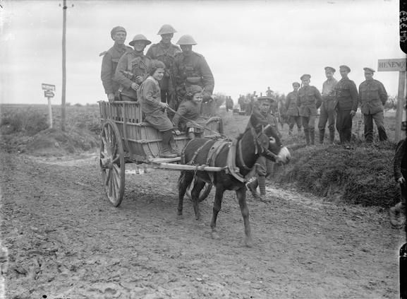 Men of the 5th Battalion, Northumberland Fusiliers in a donkey-drawn small cart driven by French children. Near Toutencourt, September 1916....