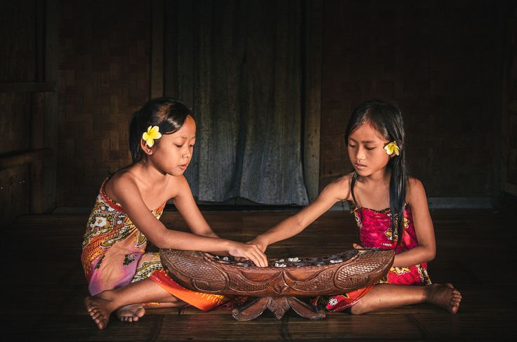 Two girls playing Congklak, a traditional children's game in Indonesia. Photograph by Ahmad Syukaery