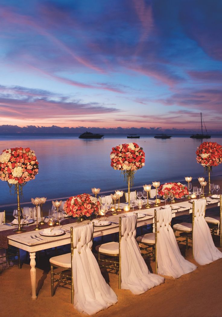 Glamorous long tablescape for a sunset beach wedding