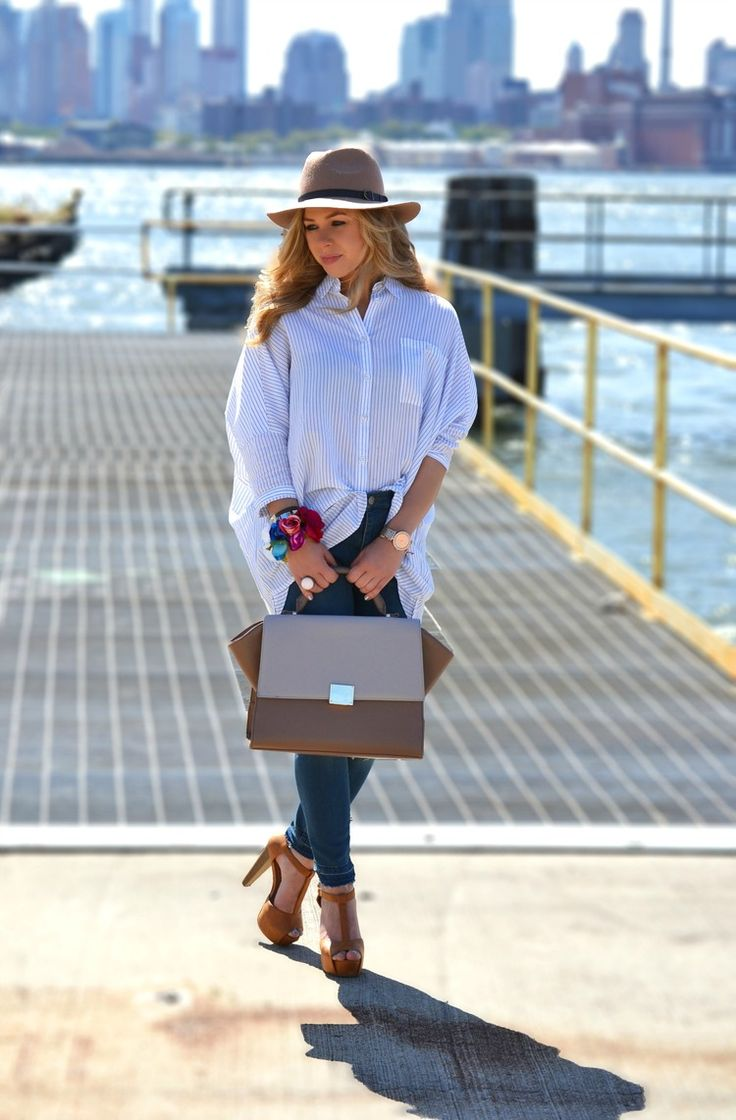 Shop this look on Lookastic:  http://lookastic.com/women/looks/hat-skinny-jeans-dress-shirt-watch-satchel-bag-heeled-sandals/4744  — Brown Hat  — Navy Skinny Jeans  — Blue Vertical Striped Dress Shirt  — Gold Watch  — Brown Leather Satchel Bag  — Brown Suede Heeled Sandals