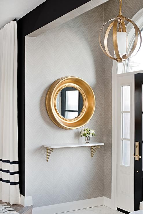 Stunning gray and gold contemporary foyer is fitted with a gold leaf convex mirror mounted to a wall covered in gray herringbone wallpaper above a brass and metal shelf illuminated by an antique brass sphere pendant.