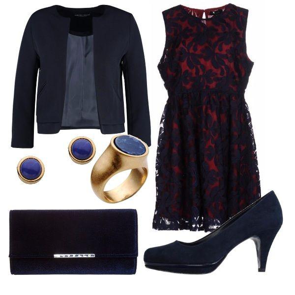 Abitino in tulle con fantasia in blu su sfondo rosso, blazer aperto sul davanti per lasciare intravedere il vestito, décolleté e pochette blu. Accessori che richiamano le tonalità dell'outfit.