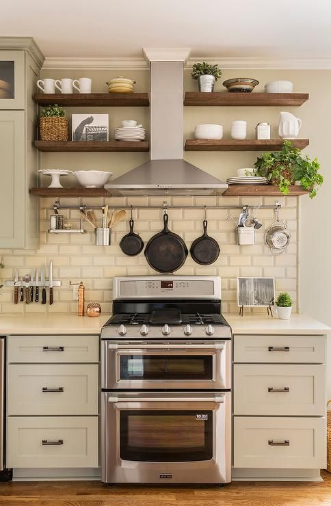 Light gray kitchen cabinets are paired with cream quartz countertops and cream beveled subway tiles, Walker Zanger Alhambra Beveled Brick Tiles.