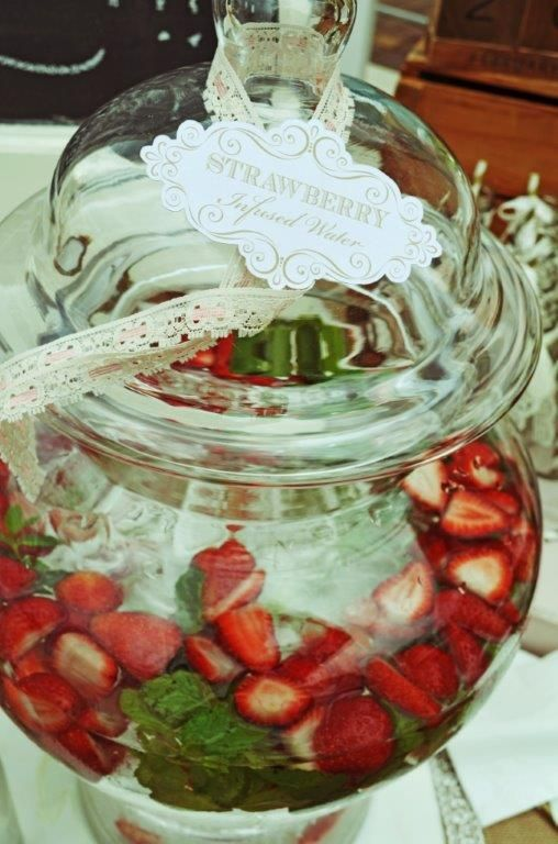 Strawberry and mint infused water in giant glass decanter