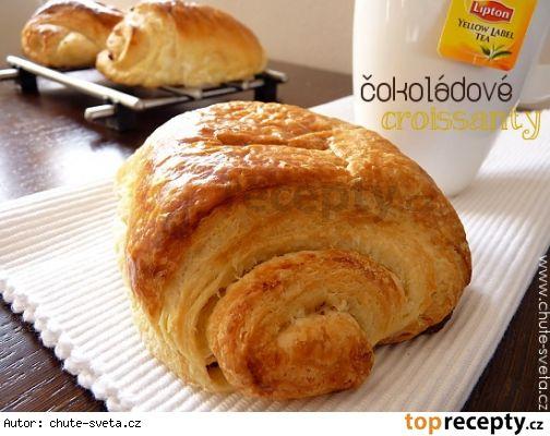 Máslový croissant s čokoládou---Suroviny: Na těsto: 3 hrnky (375 g) hladké mouky (plus navíc pro posypání válu) 1 PL (9 g) instantního droždí 1/4 hrnku (50 g) cukru 1,25 KL (7 g) soli 1,25 hrnku (300 ml) studeného plnotučného mléka 2 PL (28 g) másla (nakrájené na kousky) Máslová náplň: 1,5 hrnku (340 g) studeného másla (nakrájeného na 3 cm kousky) 2 PL (16 g) hladké mouky Na dokončení: 225 g hořké čokolády (jemně nasekané) 1 rozšlehané vejce (na potření croissantů)