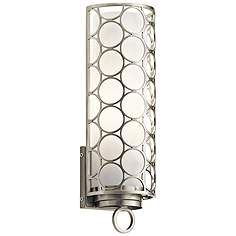 A curved steel shade, decorated with a cool circle design, stylishly covers this contemporary wall sconce.