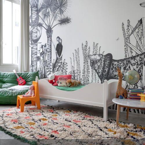Das Kinderzimmer wird von einer Wandtapete mit Dschungel-Motiv in den Farben Schwarz und Weiß dominiert. Der gemusterte Teppich, das Sofa in Grün und der gelbe…