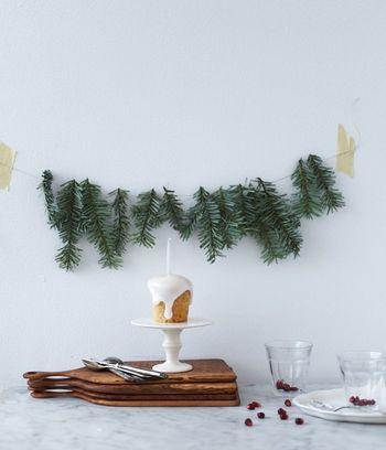 モミの木の枝を壁に紐で引っ掛けただけでオシャレな装飾に。セイヨウヒイラギの実があればクリスマス感が一気に上昇。