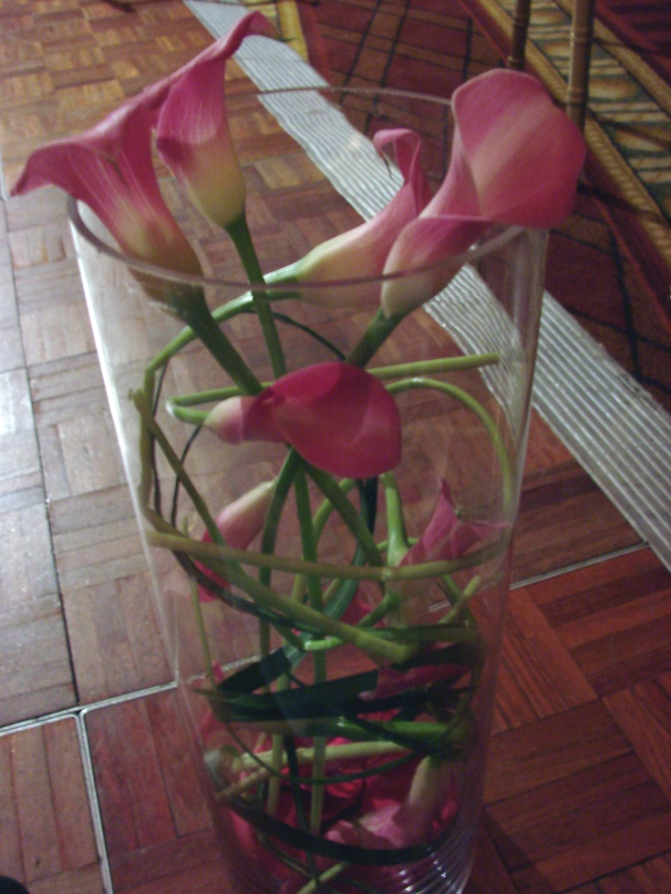 This is a floral arrangement that features pink calla lilies swirled inside a tall cylinder vase.