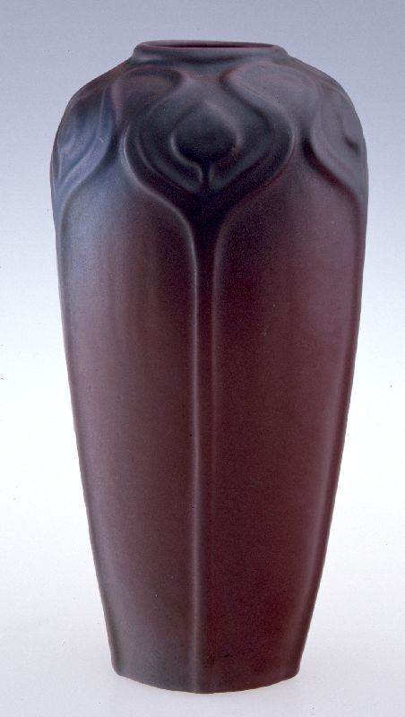 Arts and Crafts Vase, Artus Van Briggle, 1920. Molded buff earthenware vase with aubergine matte glaze graduating into blue near top in a raised stylized floral motif.