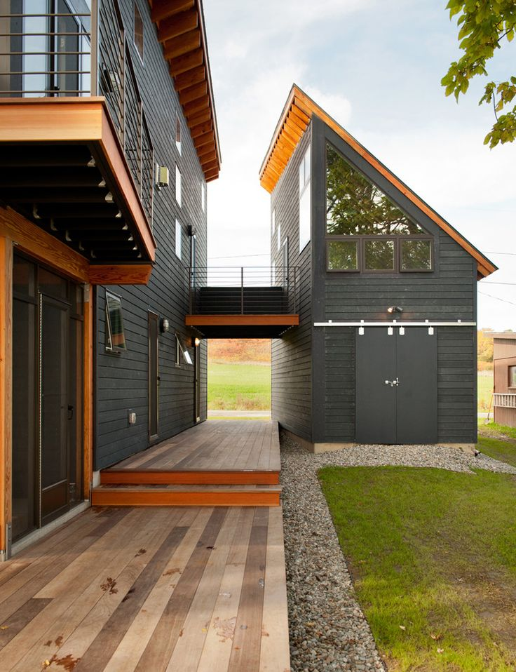 Black House with angled roof balcony barn doors breezeway catwalk forced perspective garage horizontal inverted roof overhang local white