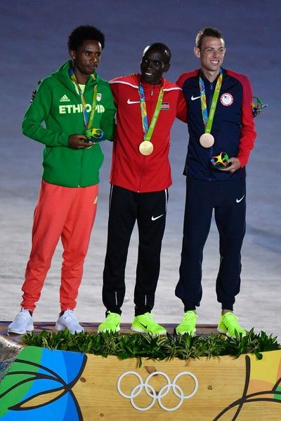 (From L) Silver medallist Ethiopia's Feyisa Liesa, gold medallist Kenya's Eliud Kipchoge and bronze medallist USA's Galen Rupp pose on the podium of the men's marathon during the closing ceremony of the Rio 2016 Olympic Games at the Maracana stadium in Rio de Janeiro on August 21, 2016. / AFP / Fabrice COFFRINI