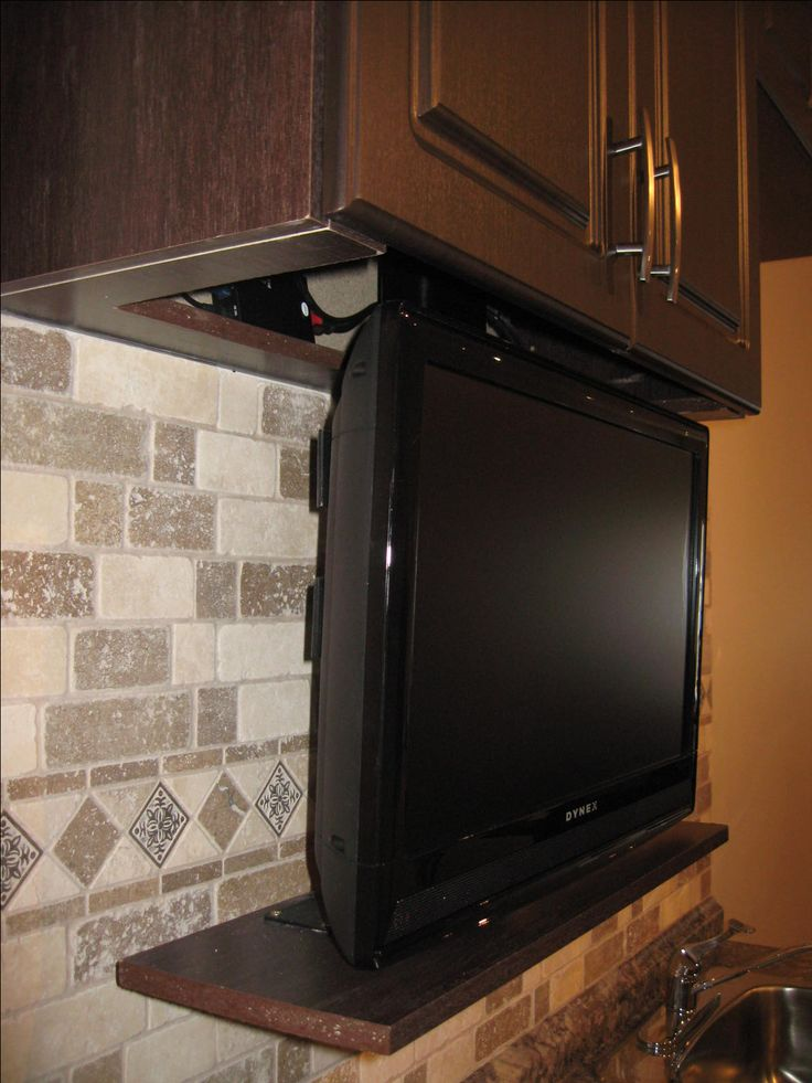close up of one of our drop down tv lift systems in a kitchen cabinet