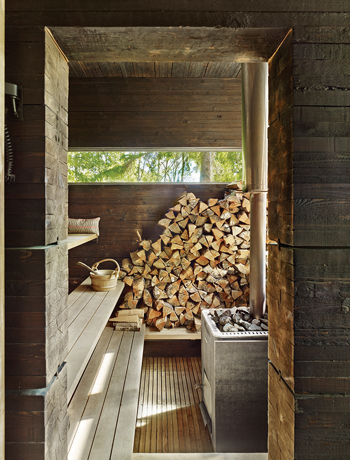 a sauna with a wood-burning stone and pine walls covered in tar